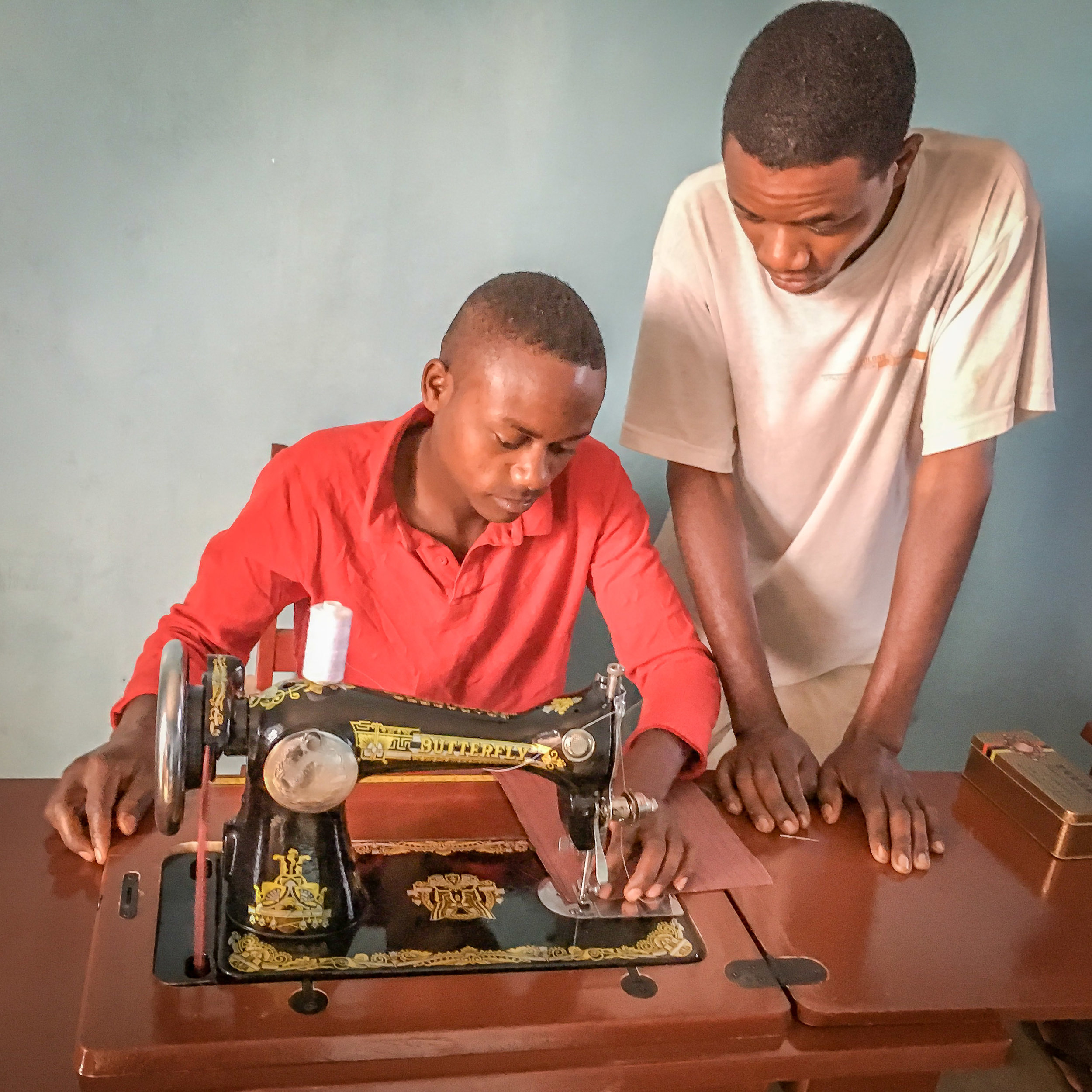 One of the young men practicing sewing while another observes.