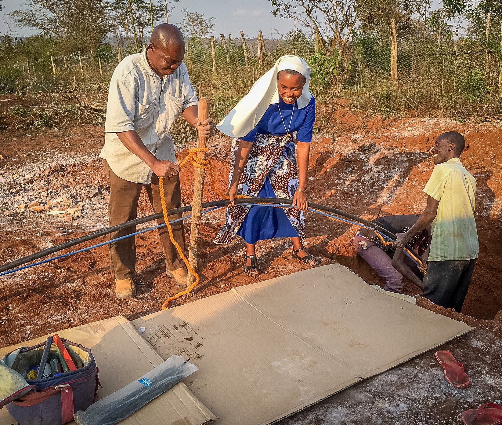 Sr. Dativa and others help send the pump down to the well.