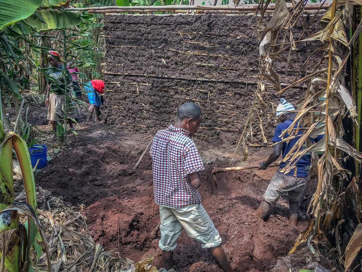 The young men in the foreground are mixing mud for the house. It is simply the existing soil mixed with water that was hauled in for the building project