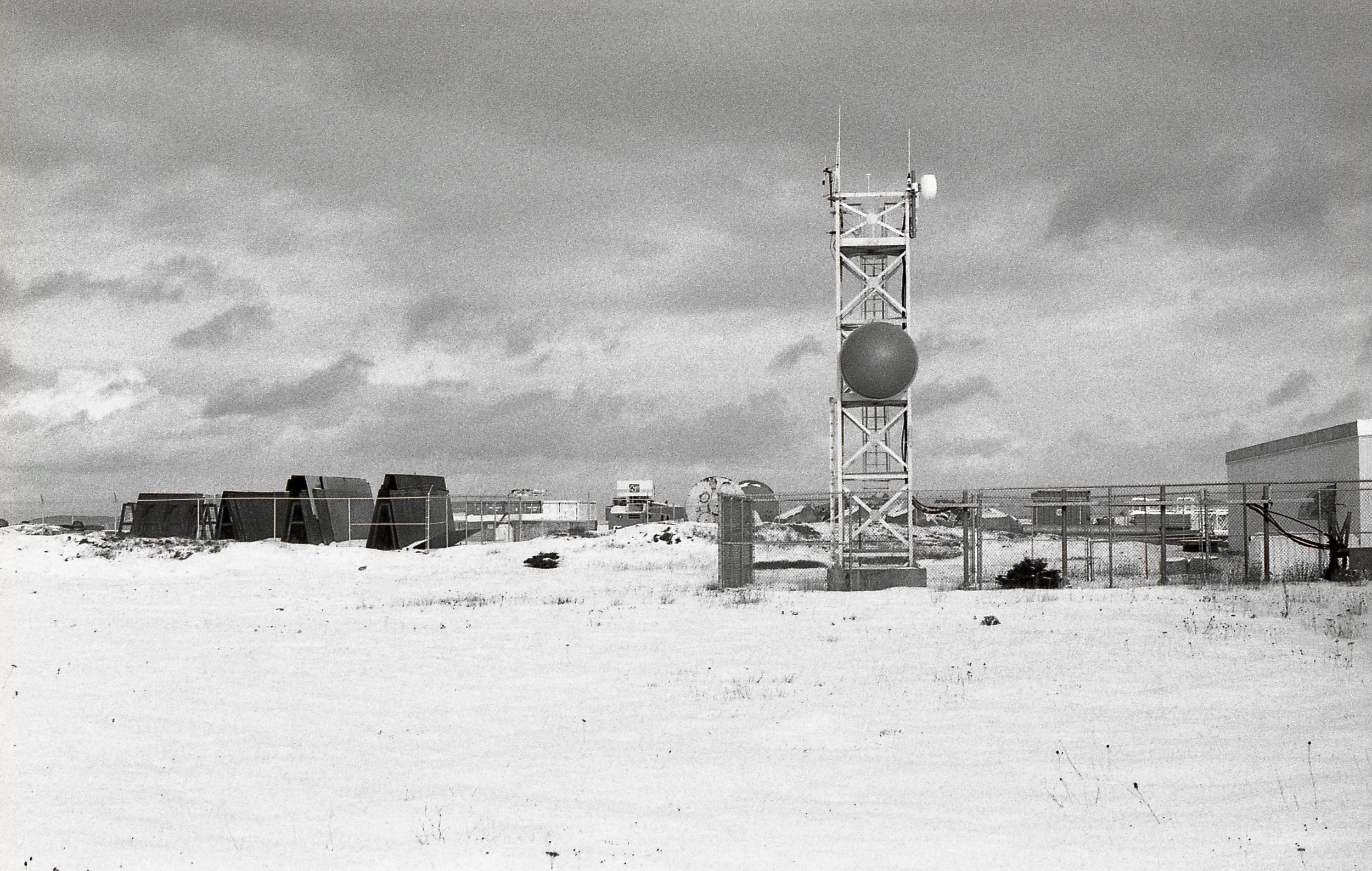 Coast Guard Communications tower at Argentia. There is a constant flow of marine traffic on the bay. Behind the tower is a storage yard of components used in constructing the new nickel processing facility.