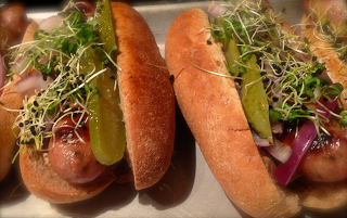 Big Fork Bacon Sausage with Polish Pickles, Onion Sprouts,Charred Onion and a Bit of Mustard