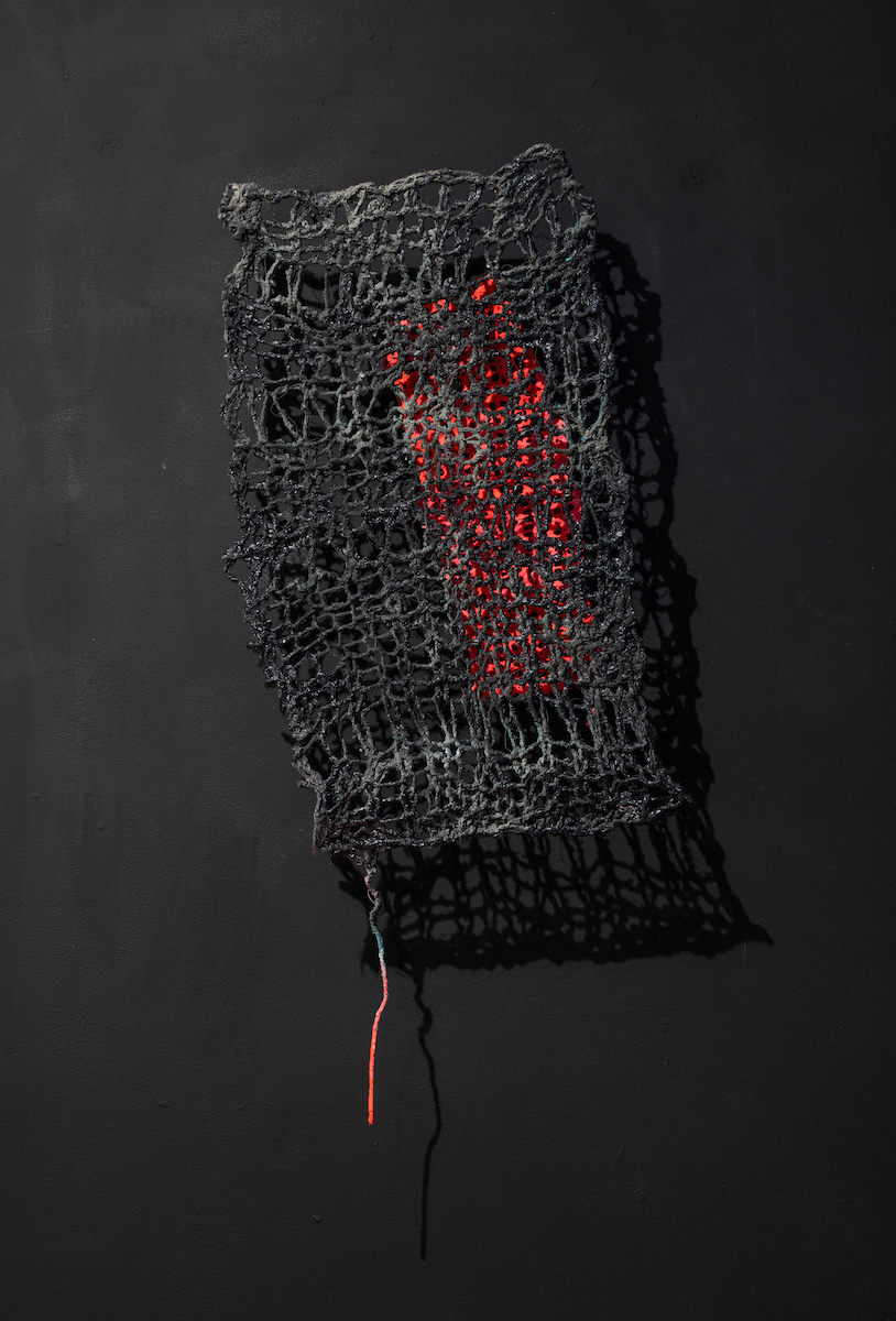 """""""Manipulated 2"""", knitted wire and yarn, cement, house paint, spray paint, 24x48""""  price: $1000  Trapped by a net of manipulation, the bright and beautiful woman still shines through the darkness of feeling trapped."""