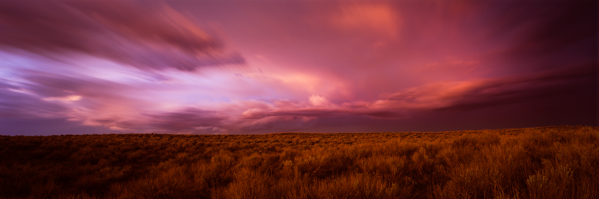 The sage brush on the Kansas prairie glows with the light of the sunset as a storm departs at highway speeds.