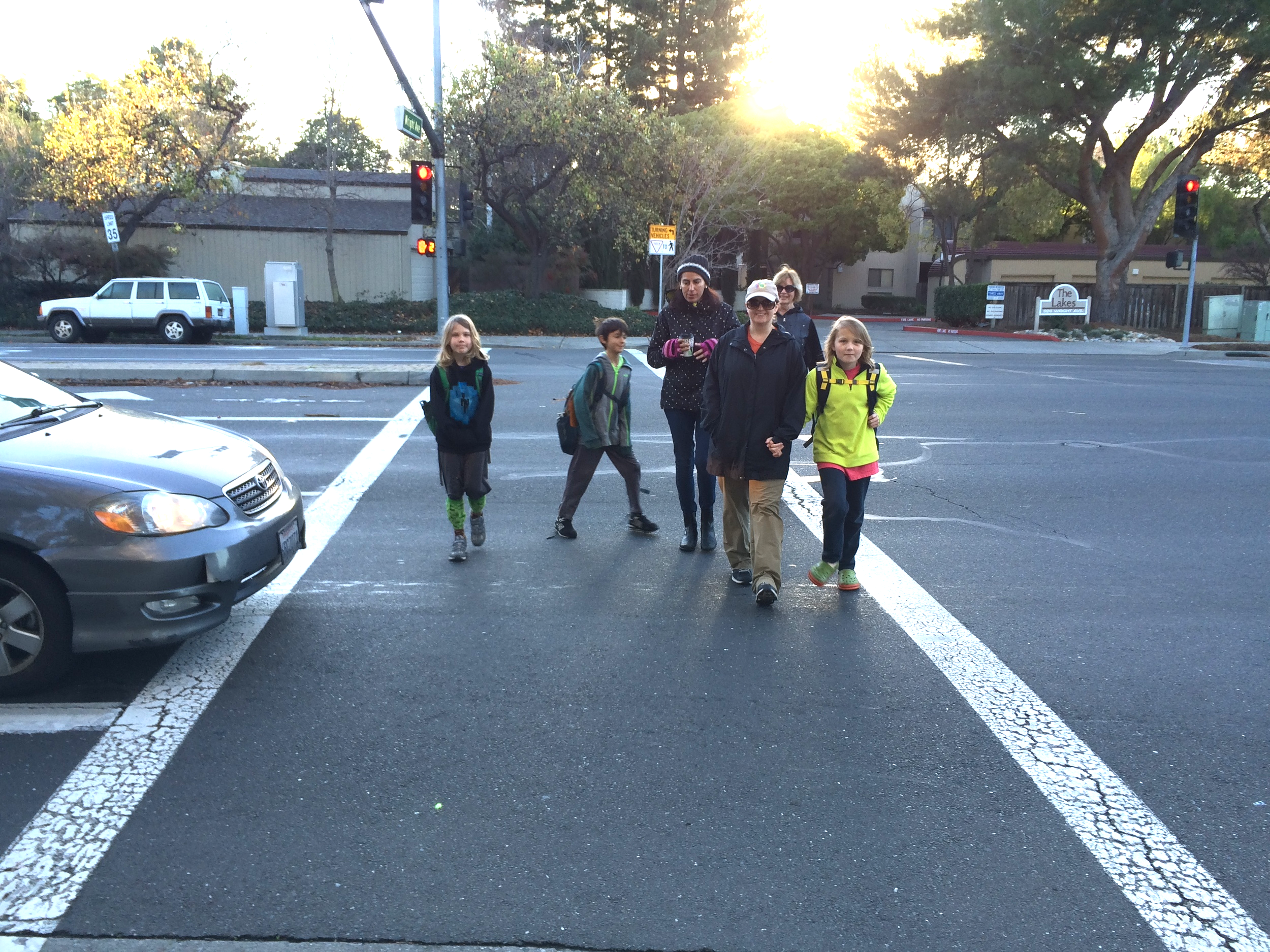 When these people have a walk signal, cars heading into the sun wait at a red light. They no longer have to worry about sun-blind drivers turning left into them.
