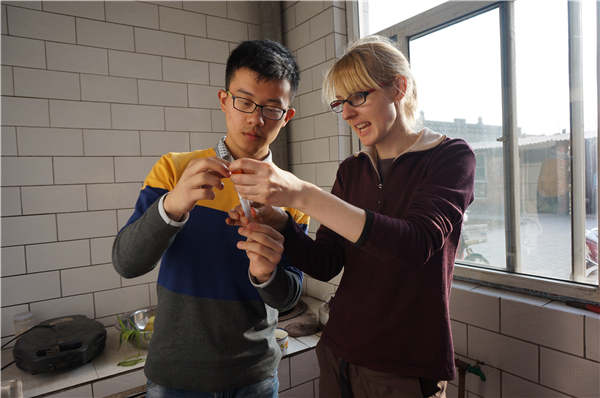 Former RISE president Kate Smith and Taiyuan University of Technology student Li Zhilin check water samples taken from Liangjiabu village in North China's Shanxi province.[Photo provided to China Daily]