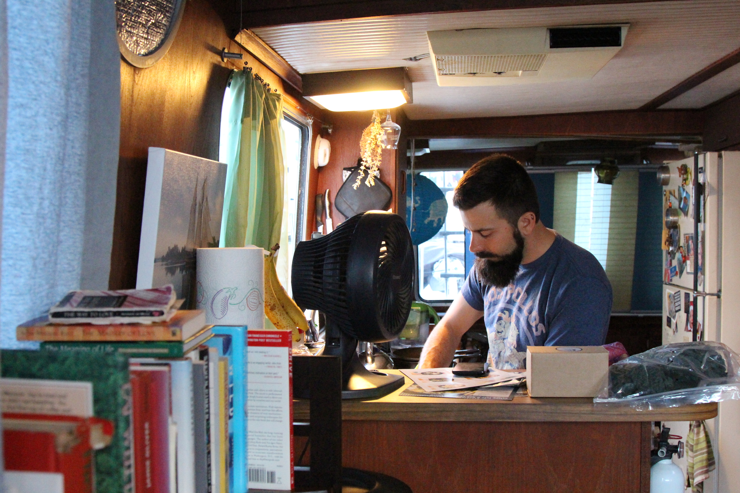 Jason Kopp cooks in his kitchen in the open space on his houseboat. Photo credit: Amel Guettatfi