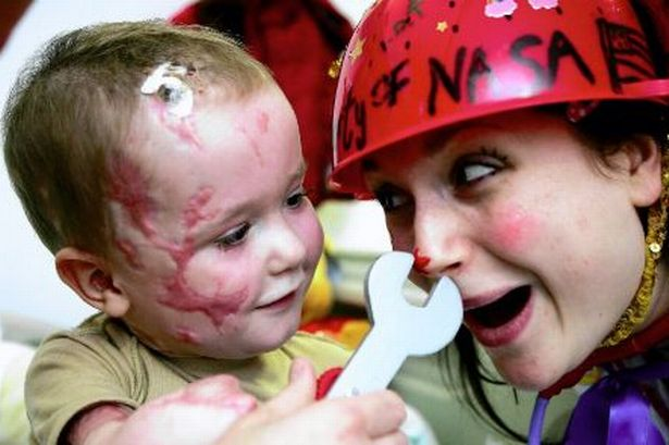 A clown doctor playing with a young patient. Credit: Manchestereveningnews.co.uk