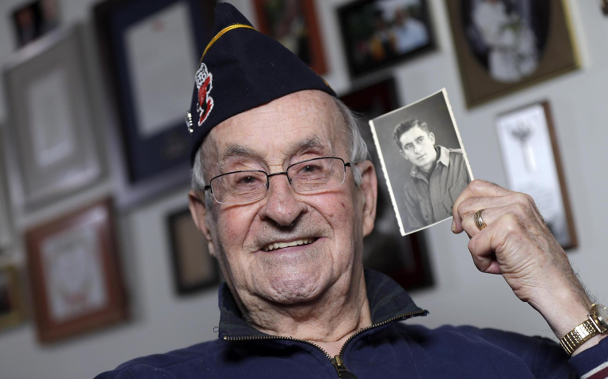 World War II veteran Ralph Ticcioni, 93, showing a photo of his younger self as a soldier. Credit: Media.jrn.com ( full link )