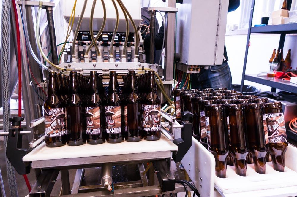 Labeled bottles entering the filler