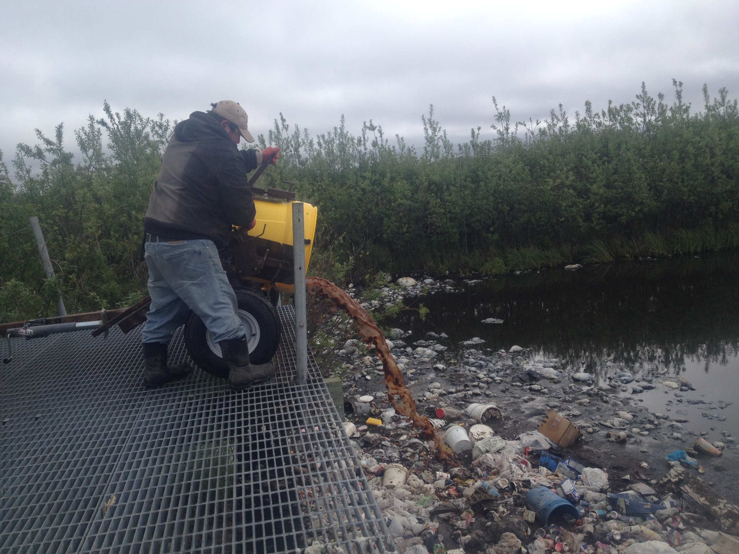 A sanitation hauler dumps human waste  from a honeybucket collection bin into a sewage lagoon.