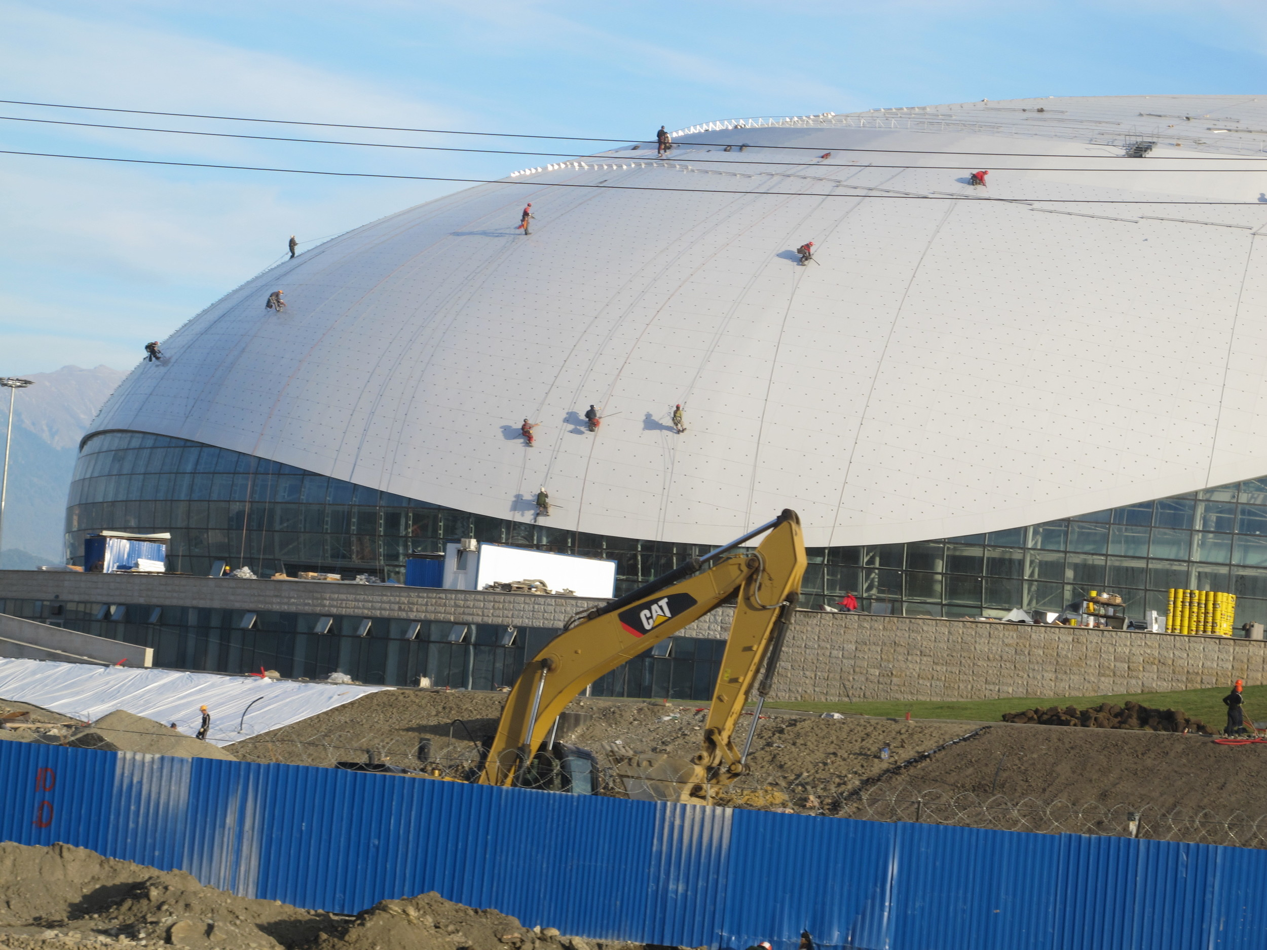 Those ant-like figures are construction workers on ropes atop the new Bolshoi Ice Dome hockey arena in the coastal Olympic complex. The roof of the dome is like a curved TV screen on which images will be projected during the Olympics.