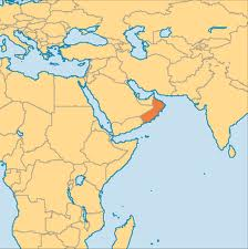 That's Oman shaded in darker tan. It abuts (from north to south on the Arabian Peninsula) the United Arab Emirates, Saudi Arabia and Yemen.