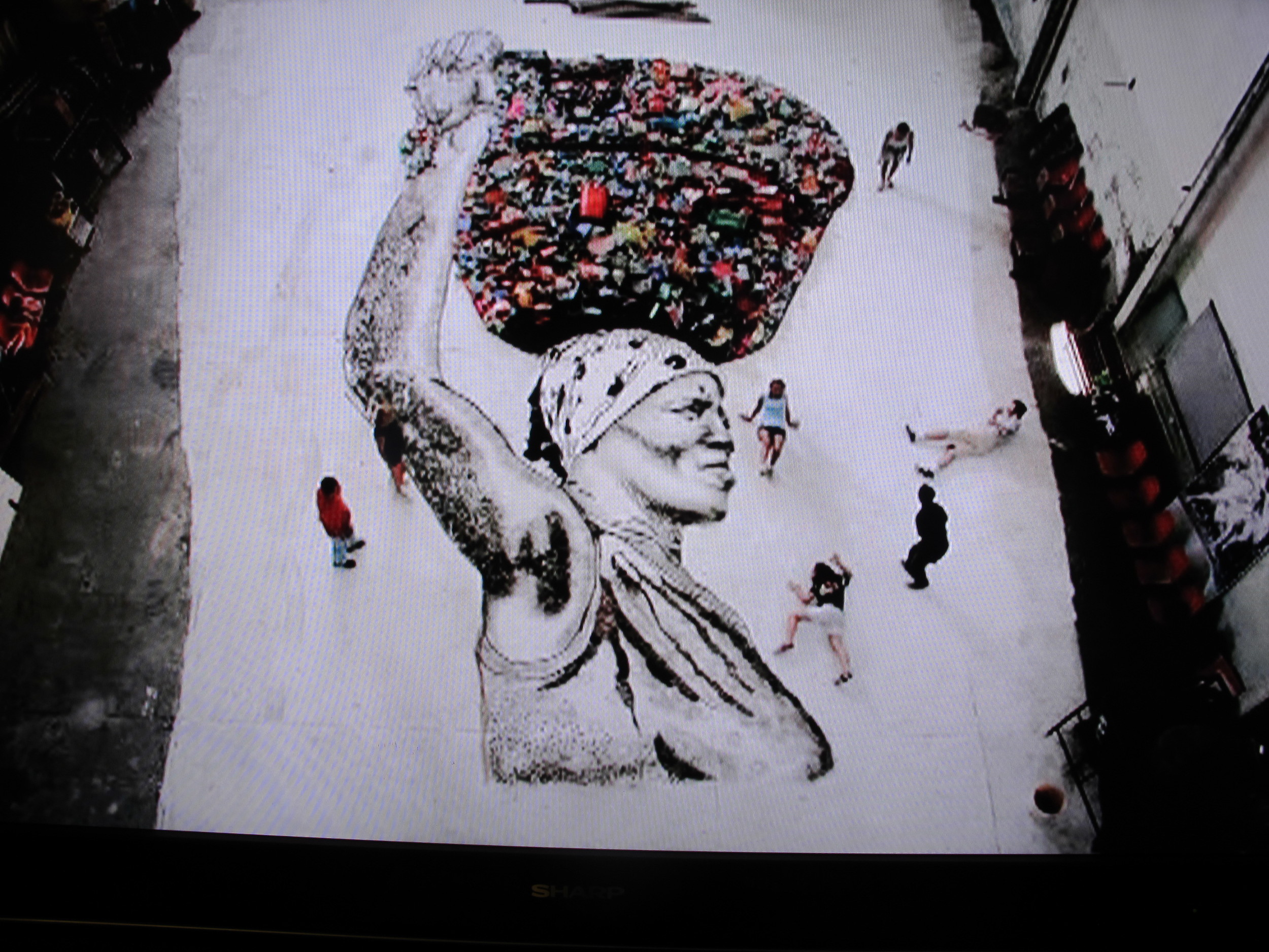 This portrait—a floor-sized blowup of a photo by Vik Muniz of one of the Rio women—was turned into art by the trash-pickers themselves, using landfill junk to outline and, in a sense, paint the image.