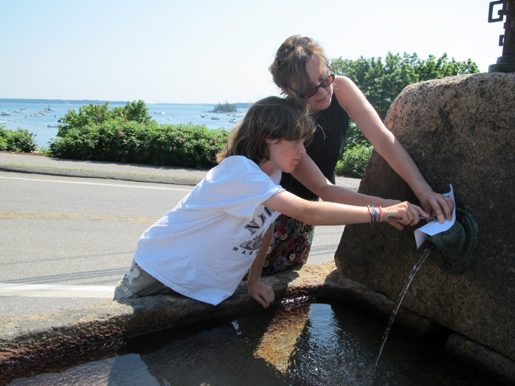 Pamelia helped hold the paper for the youngest artist, Noah, as he did a rubbing on the Seal Harbor fountain.