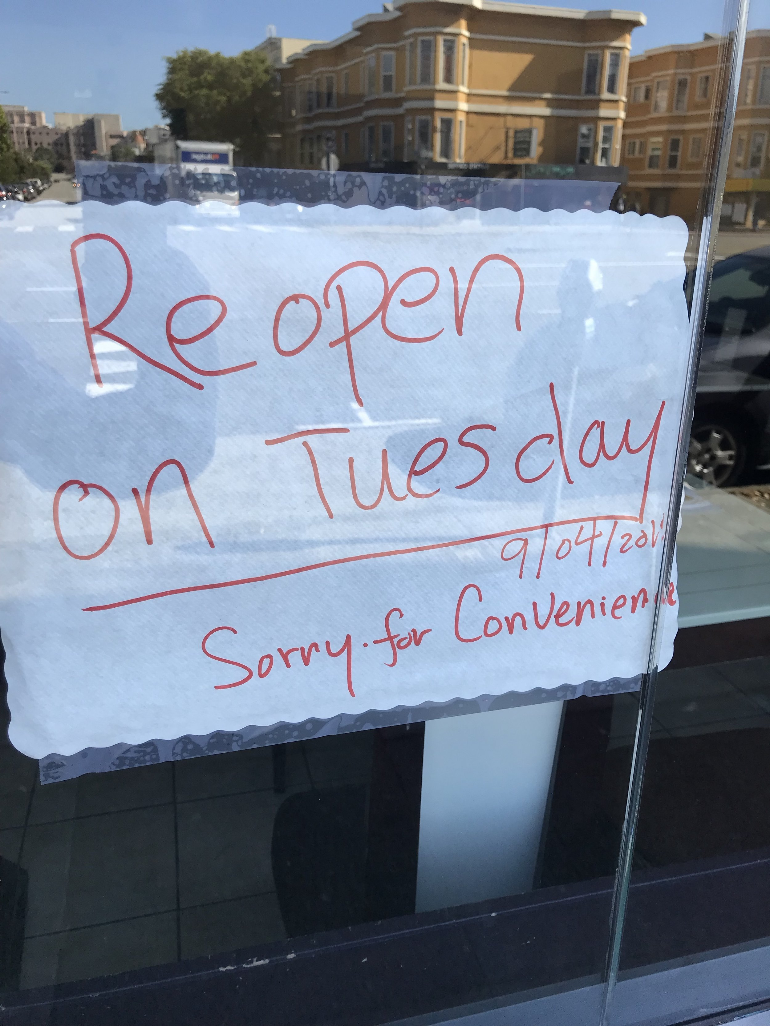 Truncated sign on window of a Thai restaurant, Geary Blvd., San Francisco, September 3, 2018 announcing a temporary closure with the kind of either/or language favored by serious writers.