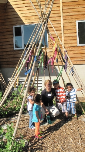 Katie with kids at an outpatient event in our sugar snap pea teepee in the Children's Vegetable Garden at the NC Botanical Garden.