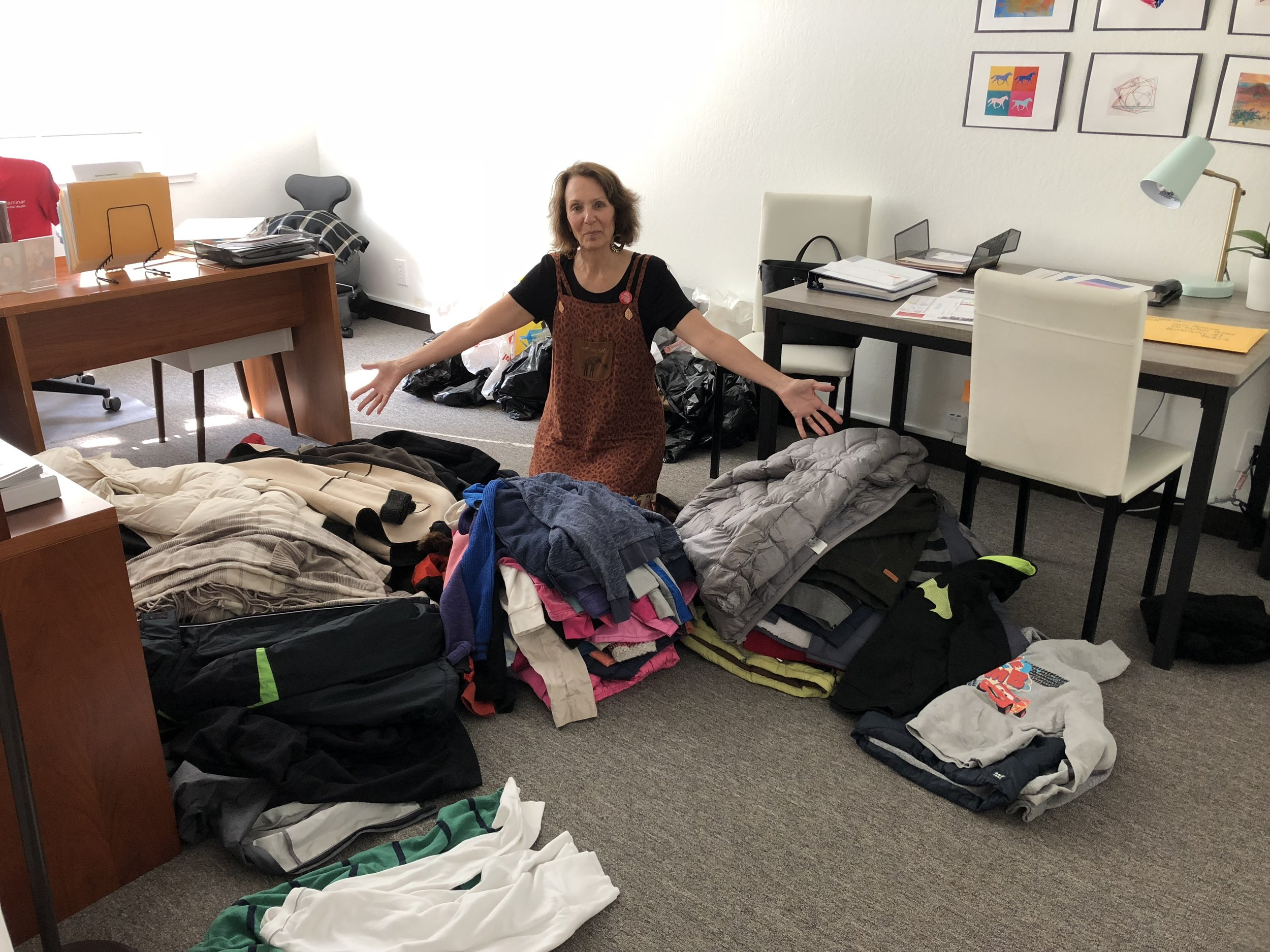 Harriet Pecot, Caminar's Director of Development, with over 100 warm coats donated by Laurel Elementary School in San Mateo.