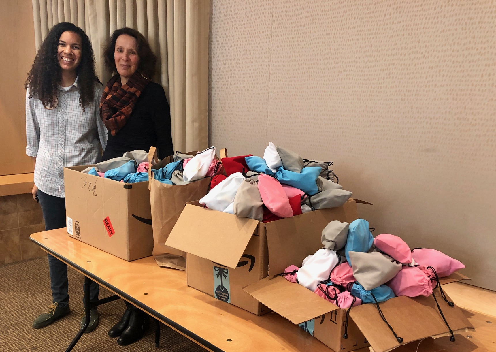 Adrienne Keel, Director of LGBTQ Programs at our LGBTQ Youth Space, and Harriet Pecot, Caminar's Director of Development, stand alongside bags of gifts for the Youth Space from the Palo Alto Rotary Club.