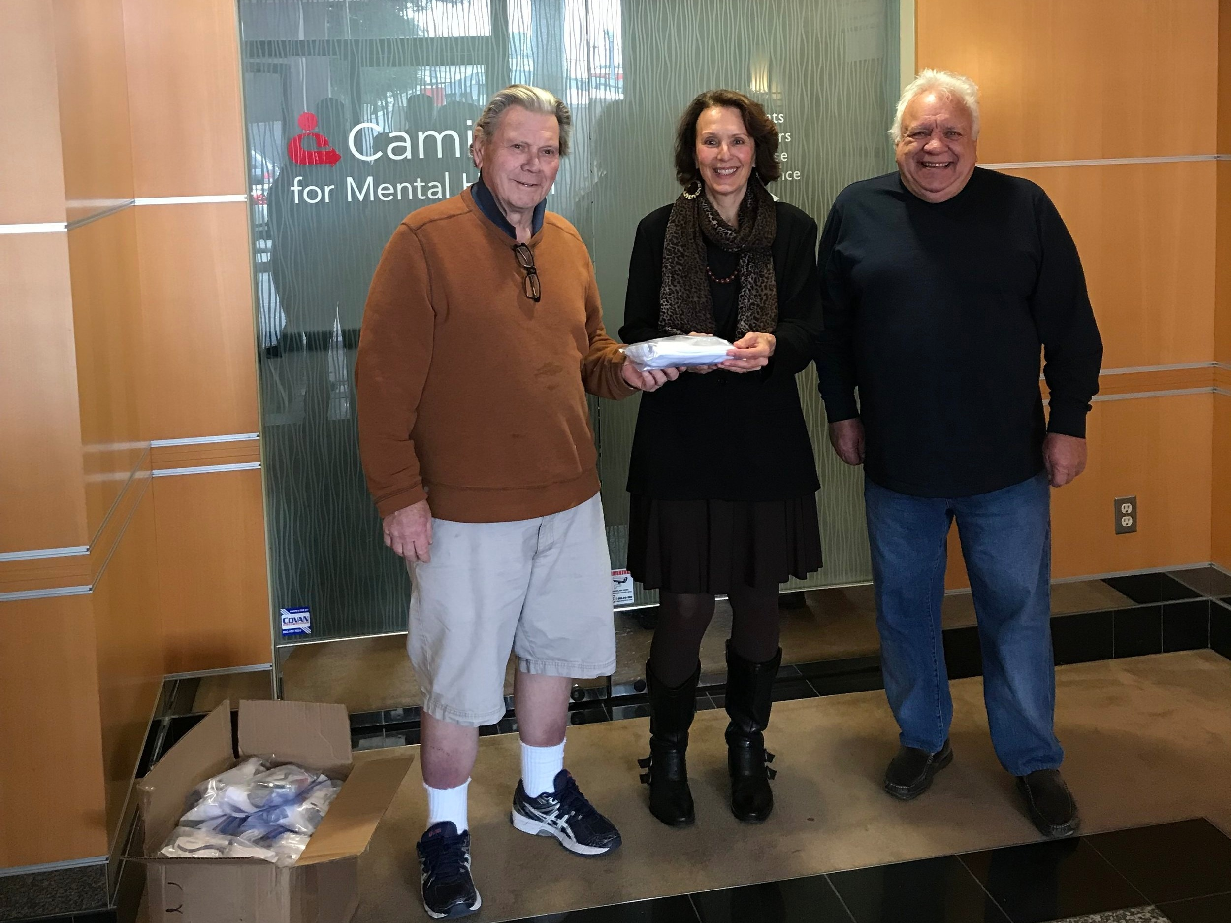 Roger Cutler (left) and Peter Cerri (right) of the Elks of San Mateo Lodge No. 1112 present Harriet Pecot, Caminar Director of Development (center), with 90 toiletry kits for Caminar clients.