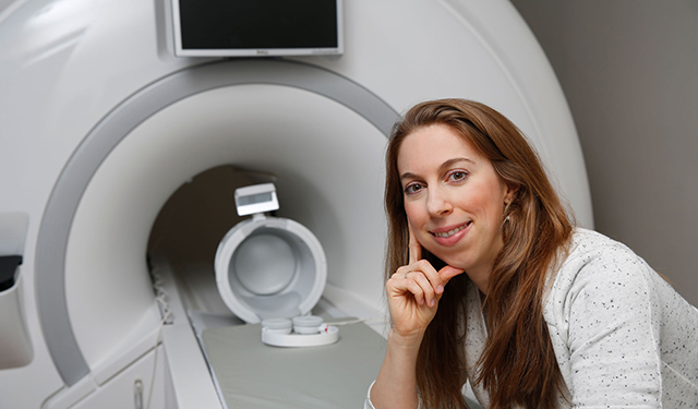 Dr. Losin poses for a photo with the mock MRI scanner.