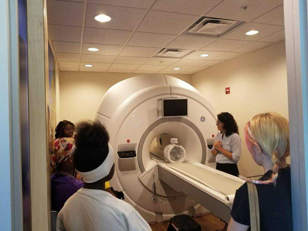 The tour included a viewing of the Neuroscience Annex's mock fMRI scanner accompanied by a detailed explanation of brain imaging by facility assistant director, Dr. Ekaterina Denkova (standing at right).