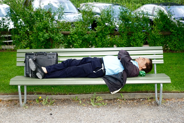business man sleeping on bench in park