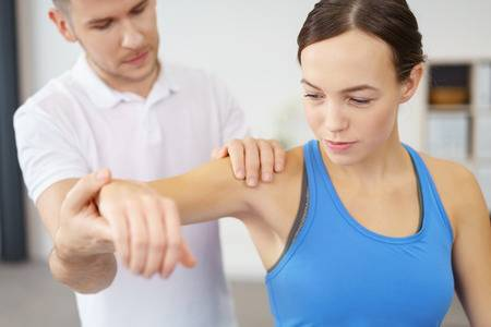49086155-professional-male-physical-therapist-helping-his-female-patient-in-exercising-the-injured-shoulder-.jpg