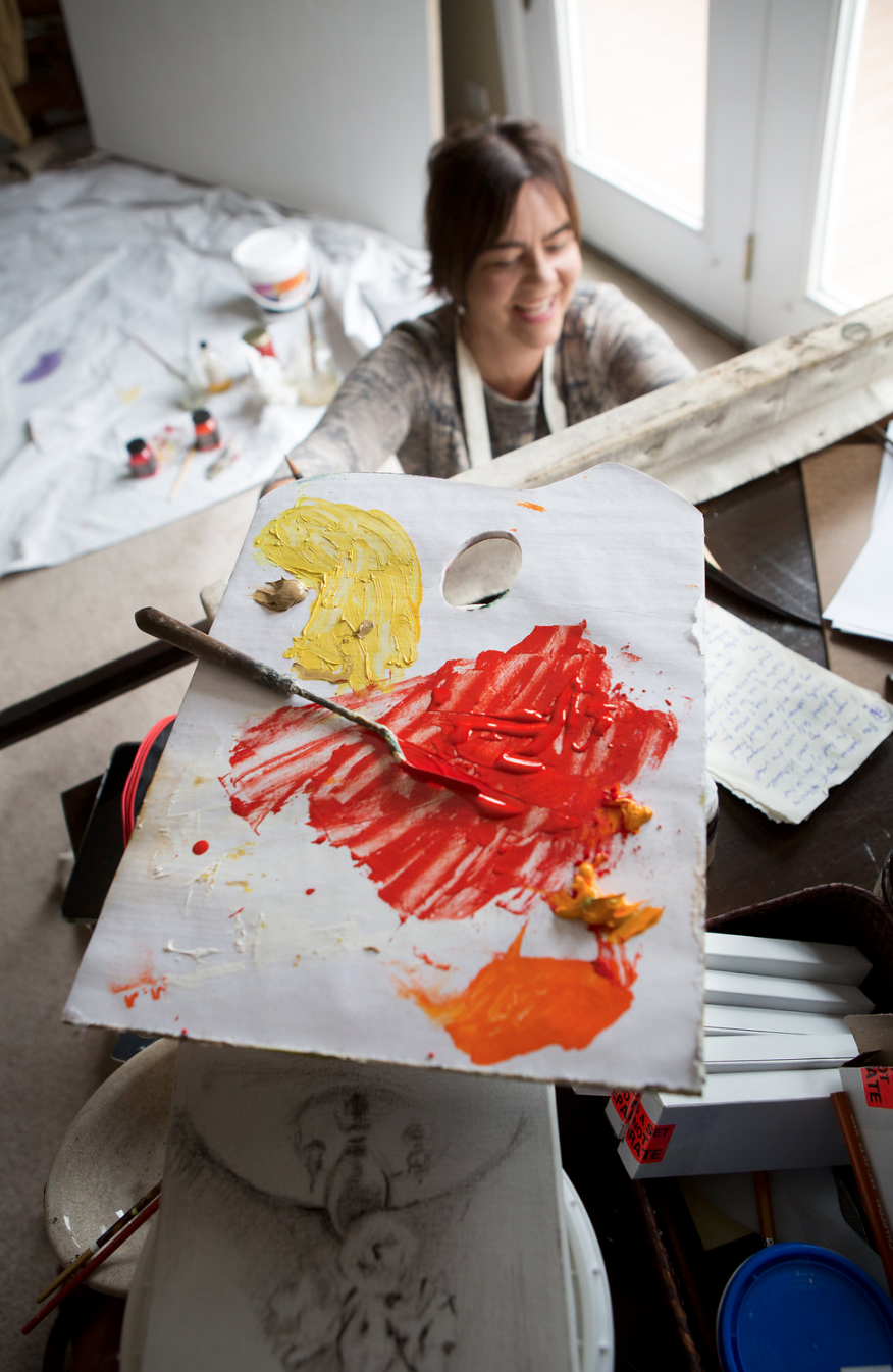 Michele Gustin working on a painting in her studio.