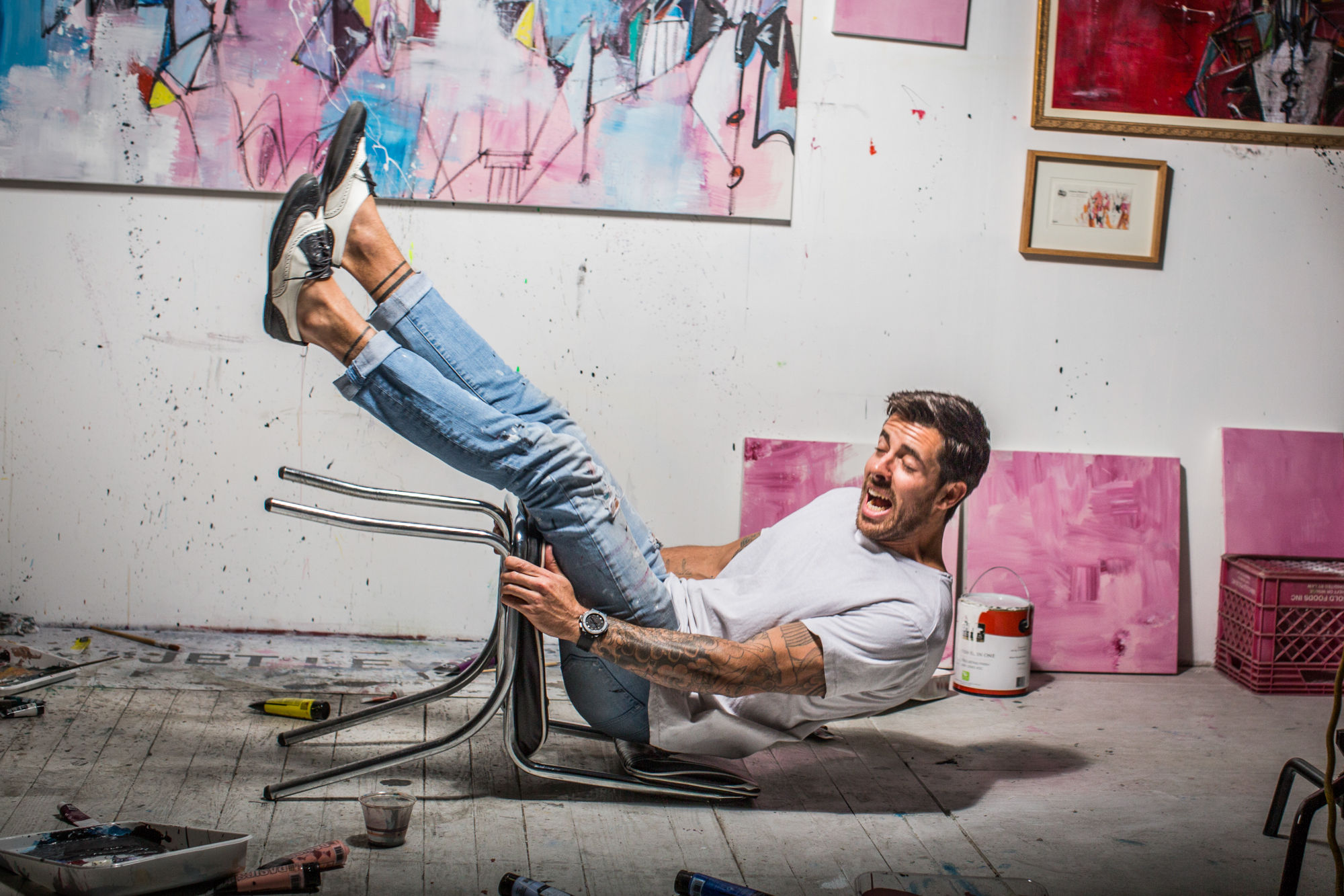 Artist in his studio falling backwards in his chair.