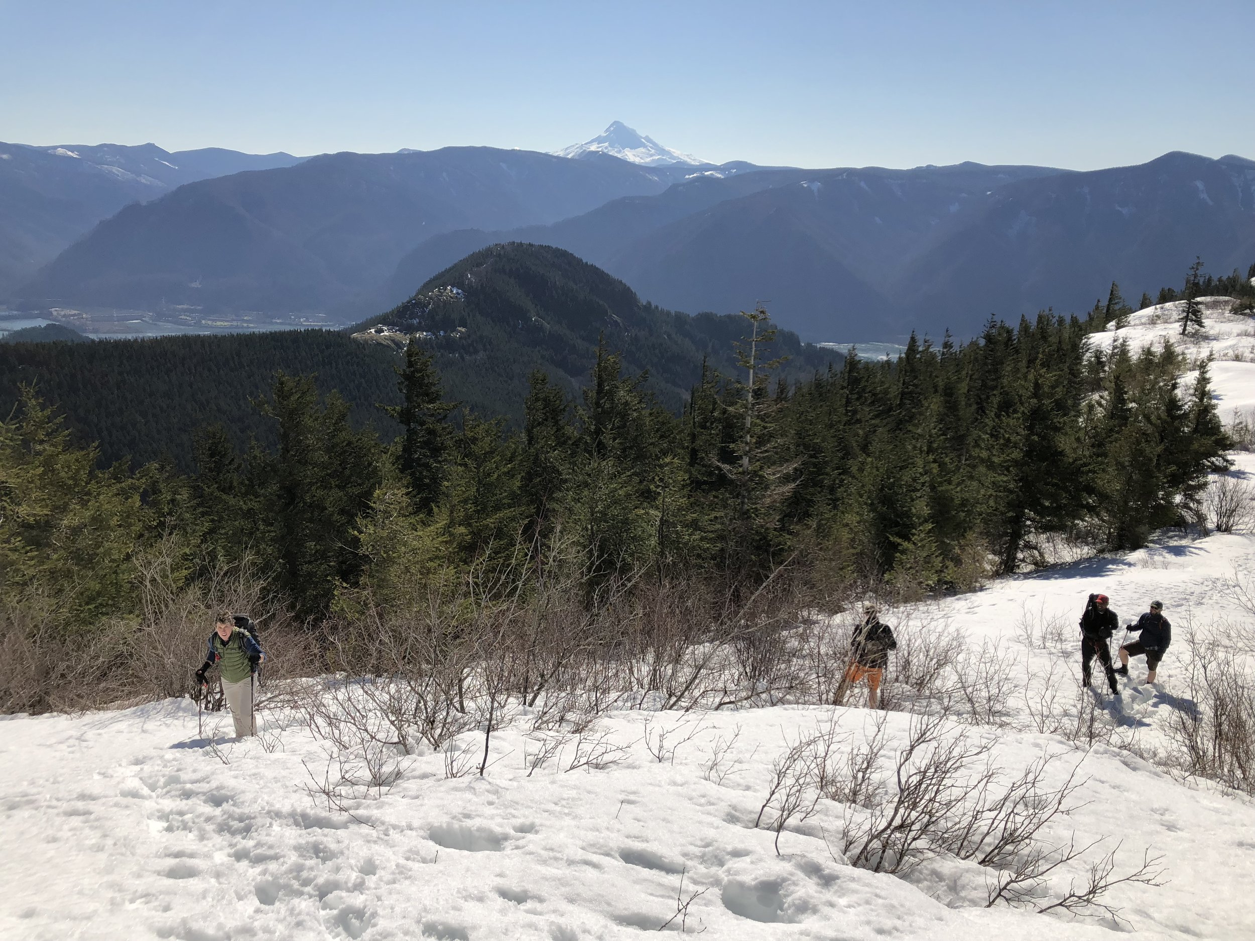 The team hiking up through the snow and nearing the summit with Mt. Hood in the distance.