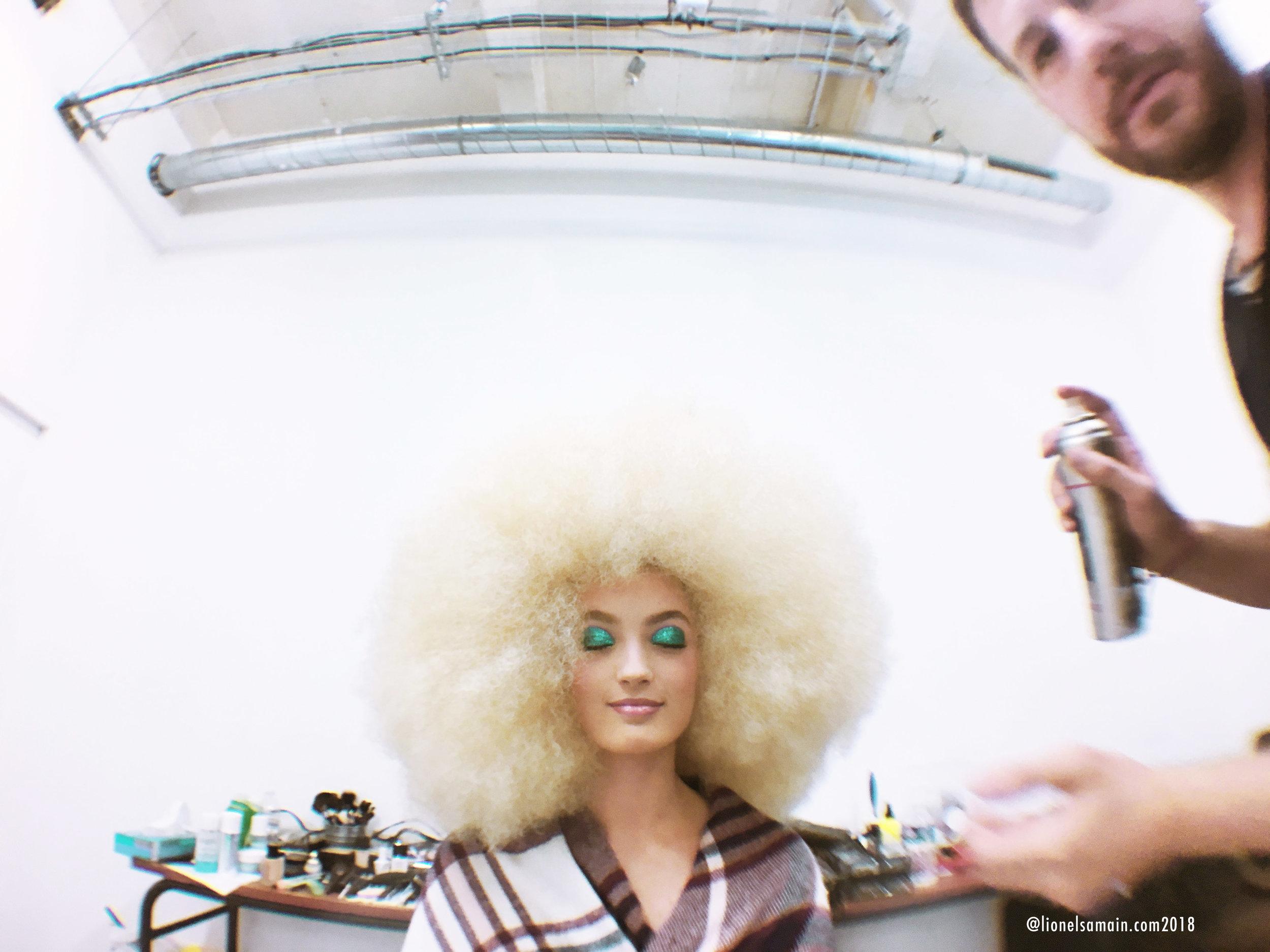 Mathieu De Mayer, make up artist and hair designer, pumping volume out of model's head.