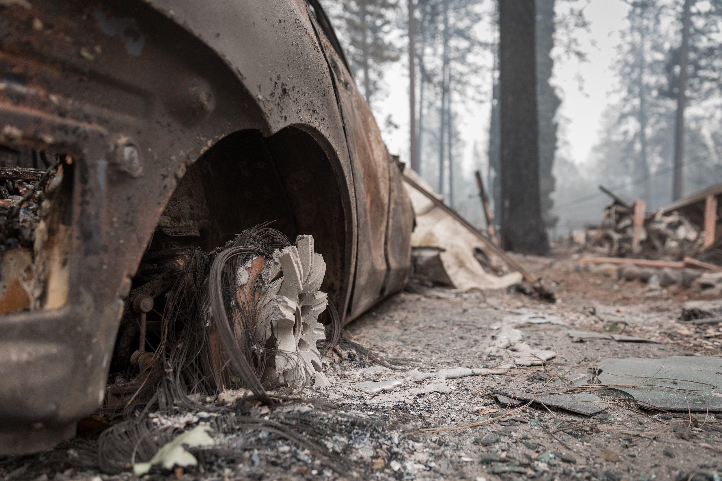 A charred vehicle sits flush to the ground after the intensity of the fire all but vanishes the tires and wheels — Paradise, CA — November 14th, 2018
