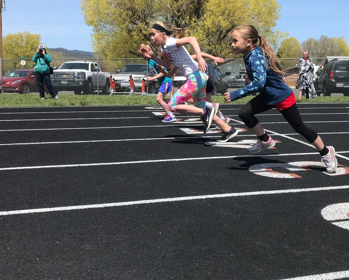A group of elementary-aged girls take off in the 100m dash.
