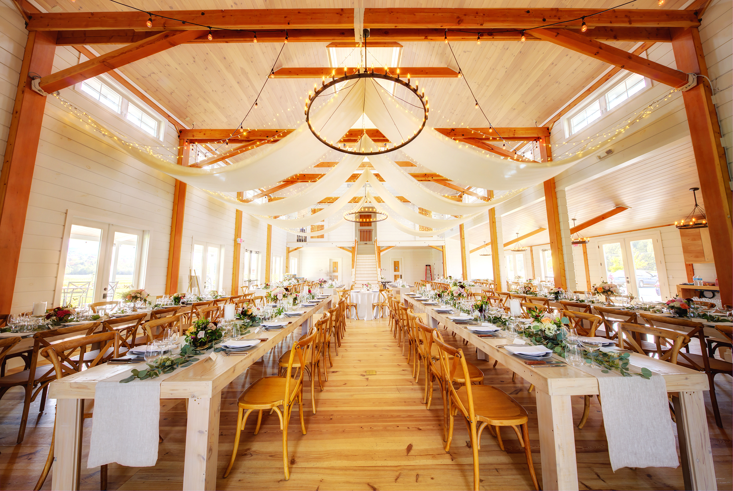 A partial view of the Main Venue Space as seen from Large Sliding Farm Doors and looking towards Central Sweeping Staircase and Bridal Suite. Image: Steve DePalma