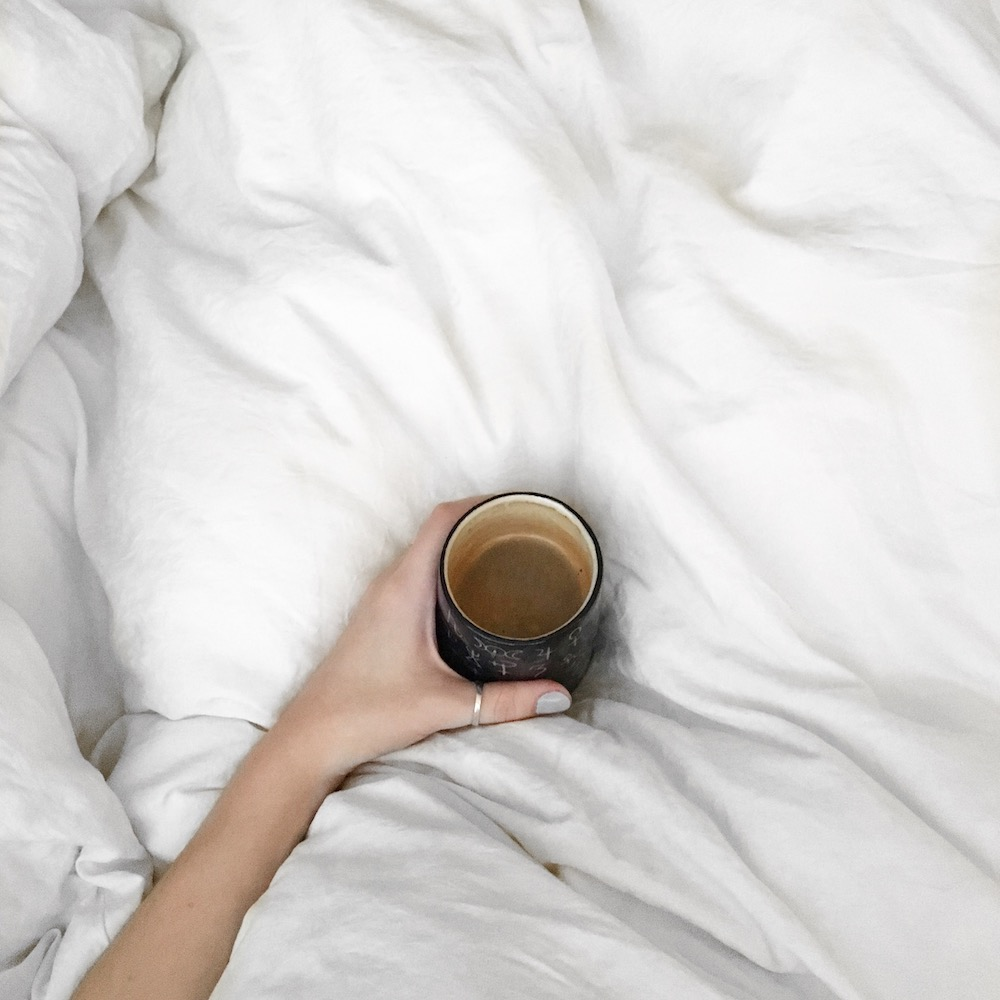coffee in bed with fluffy white sheets and a Ghost Mountain tumbler