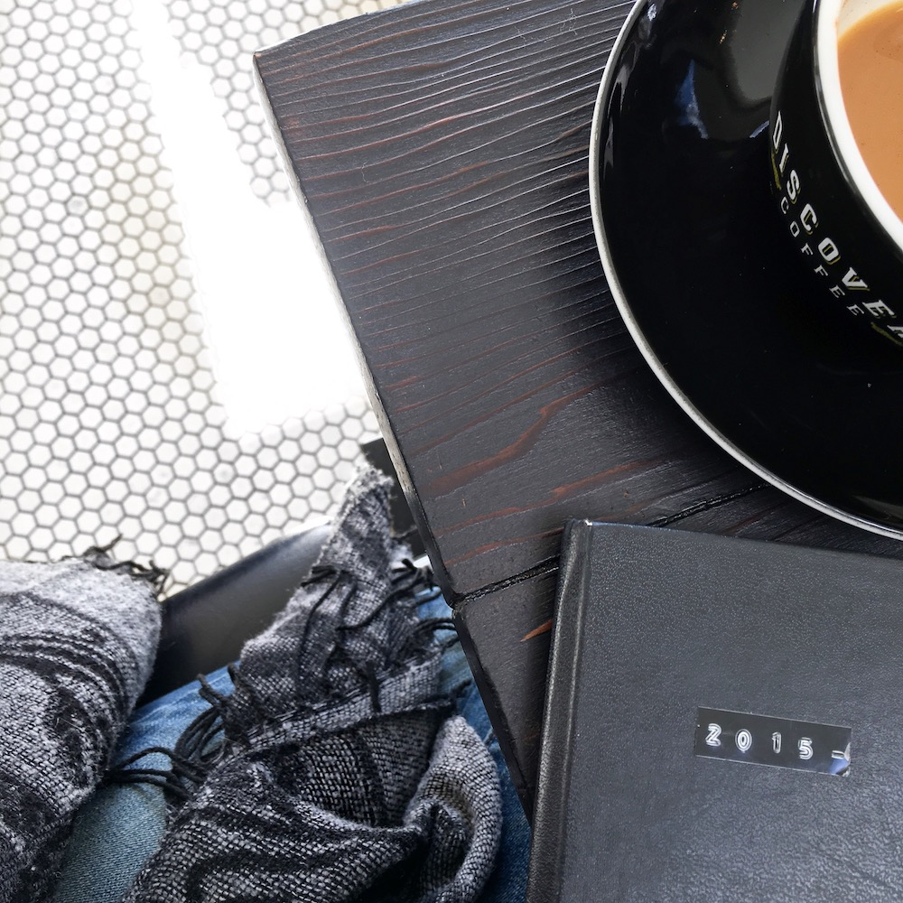 discovery coffee on a dark wood table with small hexagon floor tiles and a moleskine journal