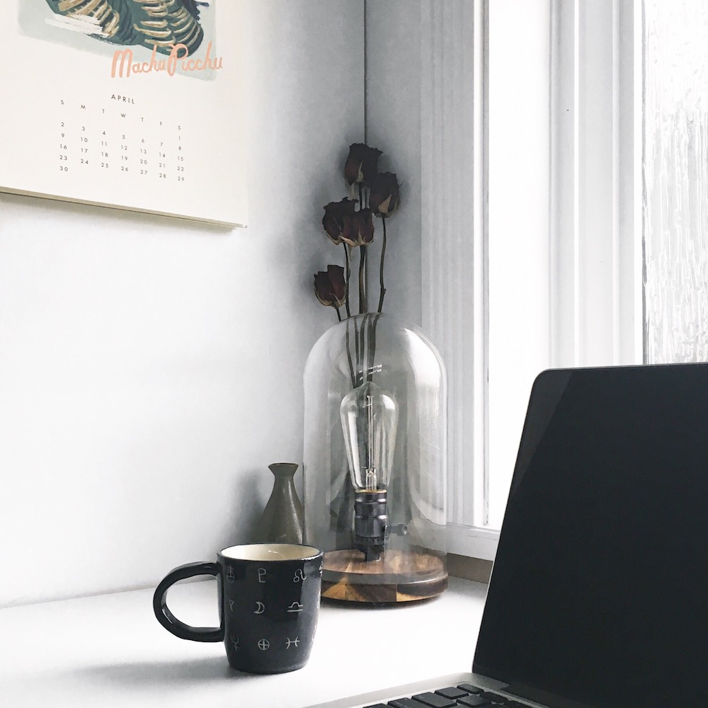 DIY bell jar lamp, cup of coffee, and MacBook Pro with a Rifle Paper Co Calendar creating the perfect study spot
