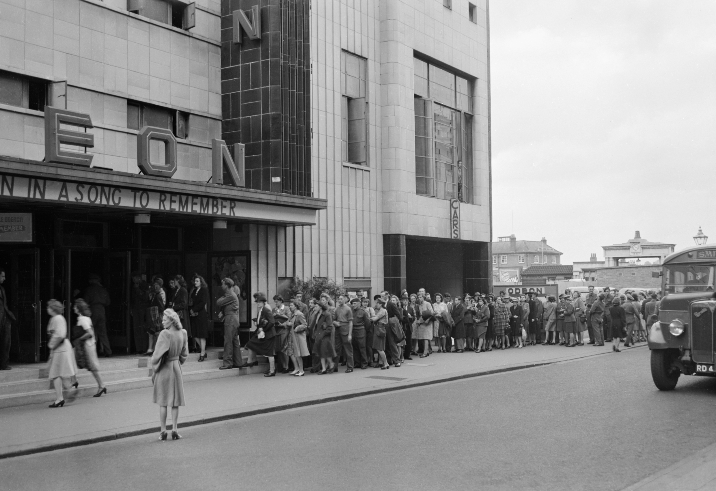 A long queue stretches out from the entrance of the Odeon Cinema in wartime Reading, as people buy tickets, 1945.  © IWM (D 25326)