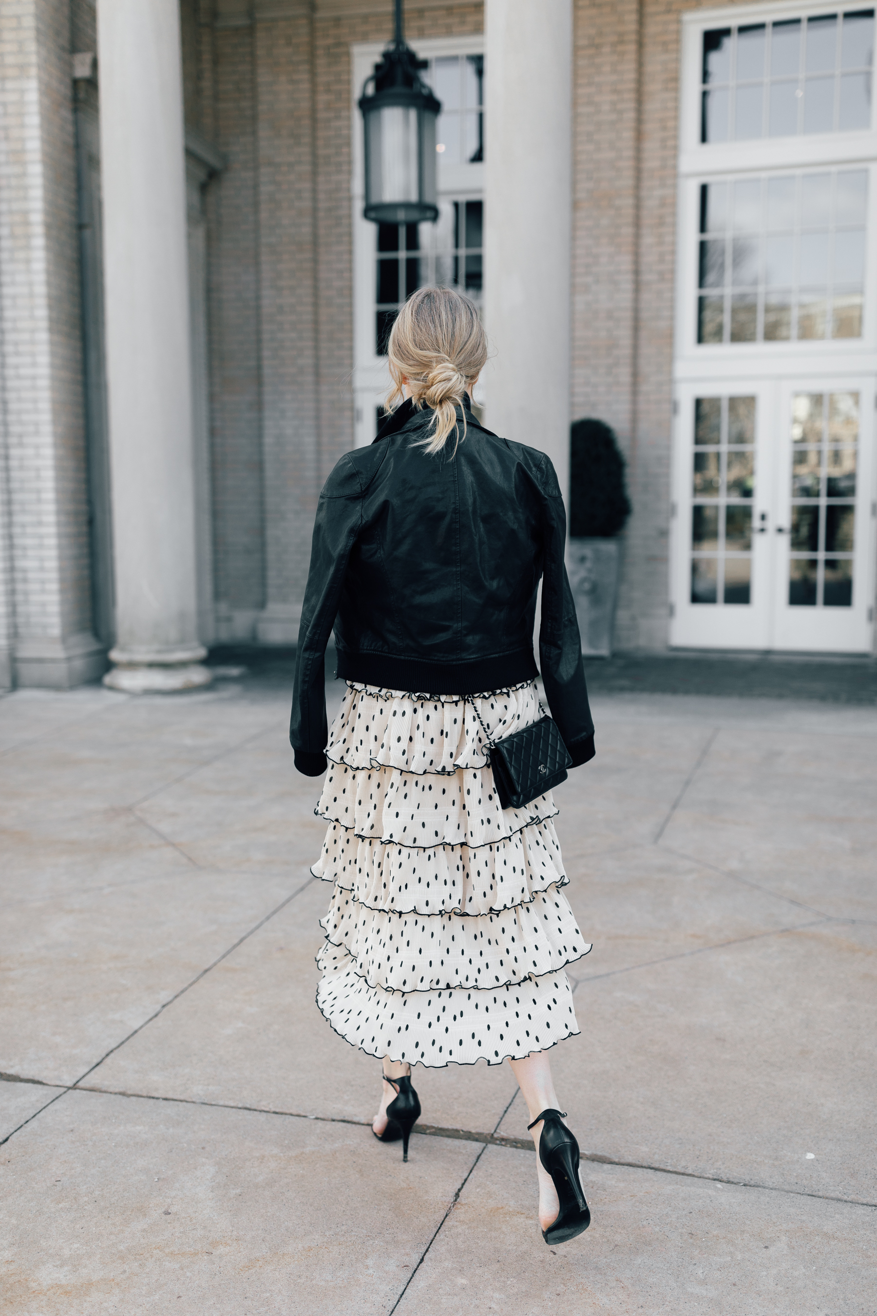 Stephanie Trotta wearing a messy chignon wearing a Ganni dress, black leather jacket, and a Chanel WOC bag