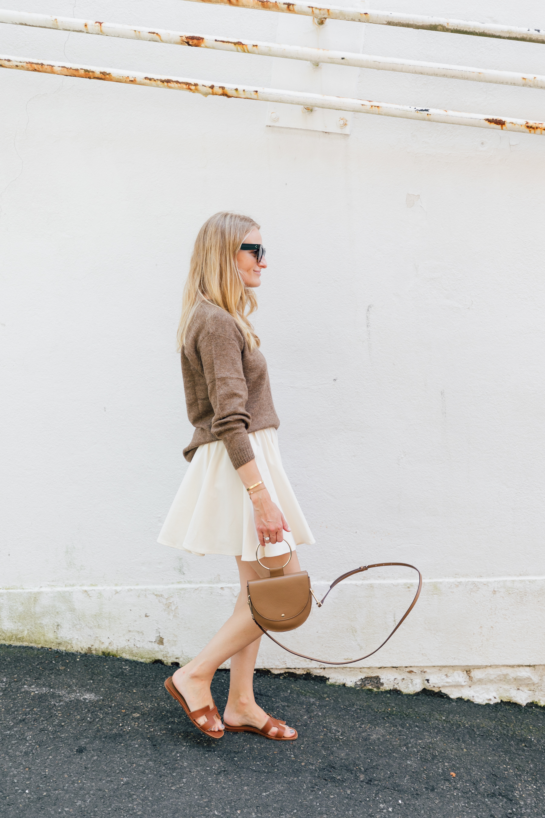 H&M mini skirt styled with a brown sweater and Hermes Oran sandals // neutral style // The Girl Guide