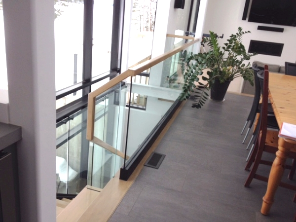 Glass track on floor with 12mm clear tempered glass guards. We used a 2x2 maple square railing channeled for the glass.  Job Location: Barrie, ON