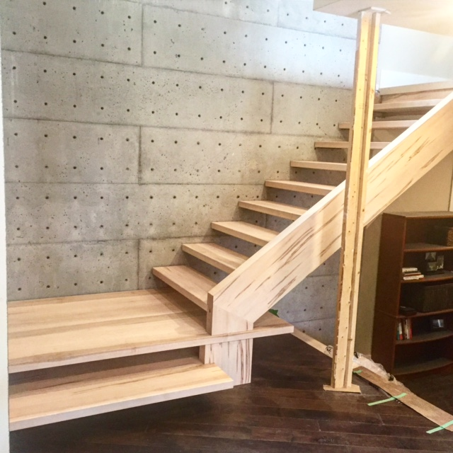 """This is amassive self support closed stringer with steel tread supports which are anchored in the concert wall. The base of the stair has a floating solid landing slab which ties into the stringer heel. We used 2-1/8"""" brown maple treads with wormy maple stringers.  Job location: Barrie, ON"""