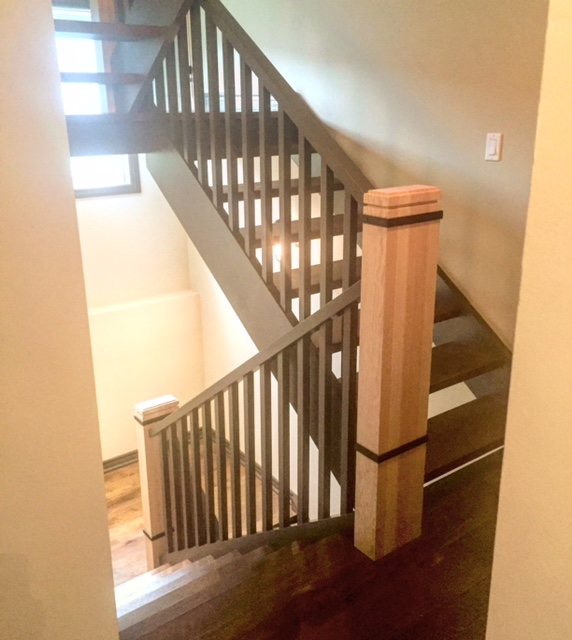 """Stairs and railings supplied & installed by Stairhaus. Closed 2 sides, open rise stair with paint grade stringers & oak treads, custom 4""""x9"""" fir posts with accent dado's and recessed steel collars. The spindles were standard paint grade 1-5/16"""" square with a rectangular flat paint grade railing.  Job location: Creemore, ON."""