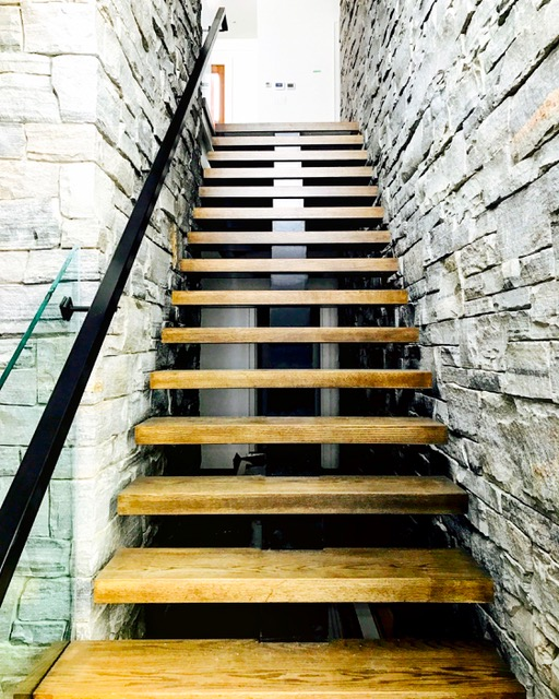 """Stairs and railings supplied & installed by Stairhaus. The specs called for custom ordered 5/8"""" clear tempered glass. The custom glass channel (not in the pic) and all hardware were special order coming direct from Germany. The glass as well was custom ordered and was coming from Calgary. The glass in the picture is cutting through the treads - super cool look.  Job location: Gravenhurst, ON."""