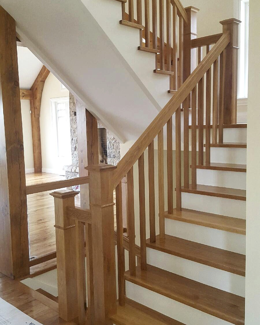 """Stairs and railings supplied & installed by Stairhaus. For the stairs, we went with paint grade risers/stringers and 1-1/16"""" hickory treads. We built our standard profile hickory railing, 4-1/2"""" square posts with caps & symmetrical moulds and hand made 1-5/16"""" square hickory spindles. We also integrated a channeled glass system using 10mm clear tempered on the main and 2nd floor level sections.  Job location: Devil's Glen, ON."""