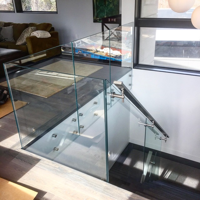 """12mm clear tempered glass with 1-1/2 stainless steel standoffs (1"""" throw). We used a flat stainless steel railing with Squareline glass brackets.  Job location: Toronto, ON."""