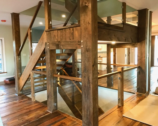"""Stairs and railings supplied & installed by Stairhaus. Closed 2 sides oak stairs with 2-3/4"""" oak treads. We used our 4-1/2"""" contemporary posts with a flat 1-3/4 x 2-1/2 oak railing. We required just over 300sqft of 12mm clear tempered glass fastened with our Squareline stainless steel clips. Job location: Horseshoe Valley, ON."""