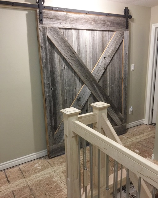 """Stairs, railings and barn door supplied & installed by Stairhaus. In this picture you can see the 4-1/2 maple shaker posts, 3-1/2"""" vertical railing with TL58-SS (5/8 stainless steel spindles) sporting square wood decoratives. We also built and installed this massive 2-sided double cross barn door out of our grey board.  Job location: Barrie, ON."""