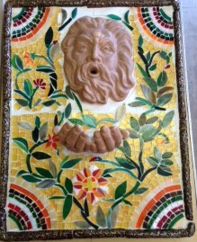 Mixed Media: Hand Built border with Glass Mosaic and Plaster Mold Cast Face and Hands. Glaze was used for the face and border.