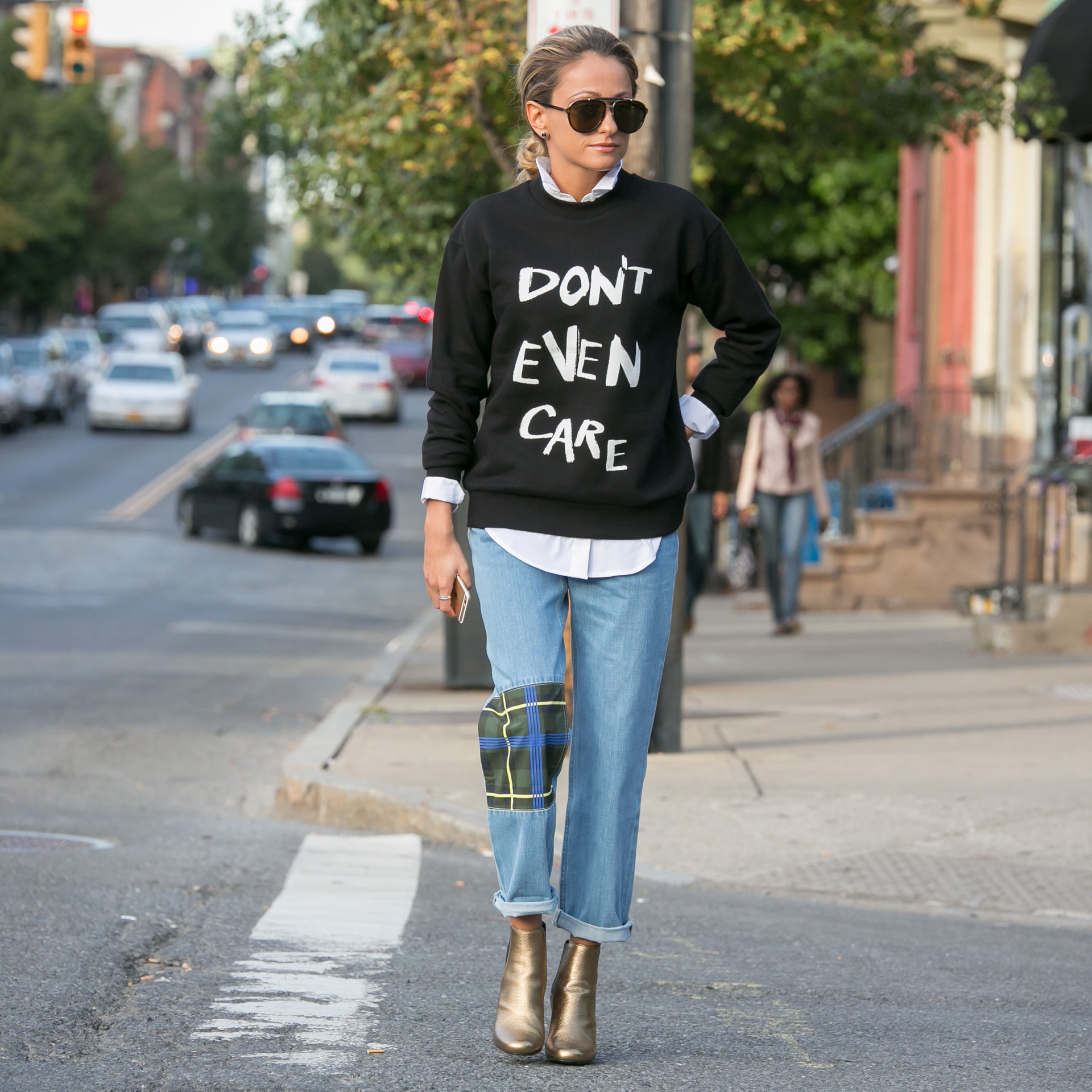 Lauren Recchia wearing Etre Cecile graphic sweatshirt and boyfriend jeans and Saint Laurent boots